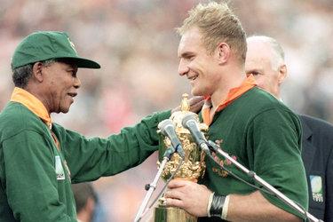Nelson Mandela, in campo con la divisa degli Springboks, consegna la Coppa del Mondo al capitano della nazionale del Sudafrica François Pienaar, dopo la vittoria nella finale vinta contro la Nuova Zelanda.